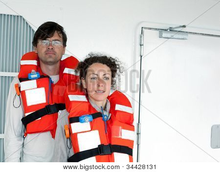 man woman wearing lifejackets are on deck of ship