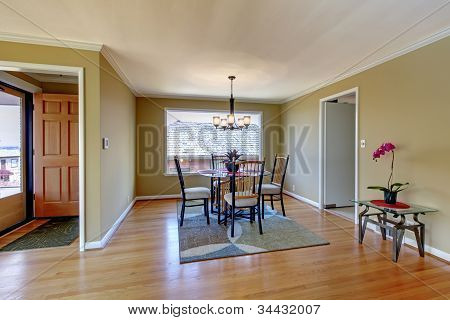 Dining Room With Flont Door And Hardwood Floor.