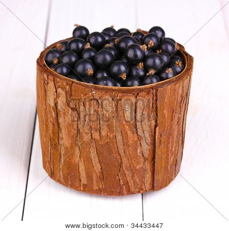 Black currant in wooden cup on wooden background