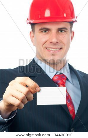 Handsome smiling engineer with hard hat on his head showing business card with space