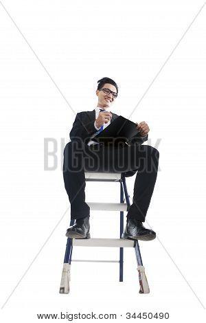 Businessman Working On Ladder