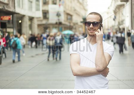 Man With Sunglasses And Cell Phone Walking