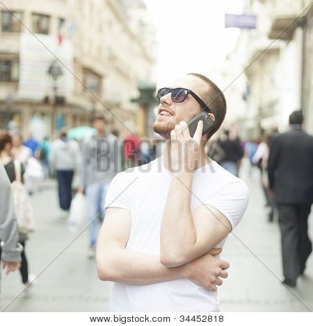Young Man With Sunglasses And Cell Phone On Street