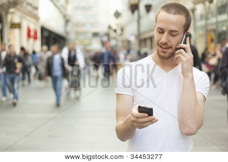 Speaking On One Mobile Phone And Holding Secund Cell In Hand