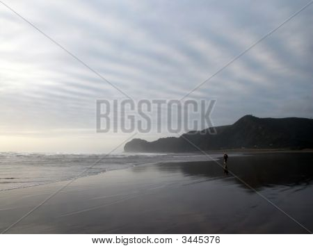 Lone Man Walking On Black Sand Beach