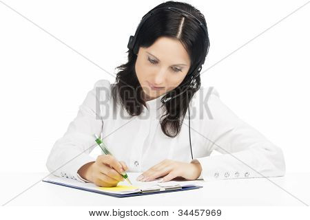 Portrait Of Busy Brunette Call-center Customer's Support Operator With Headset  And Writing A Docume