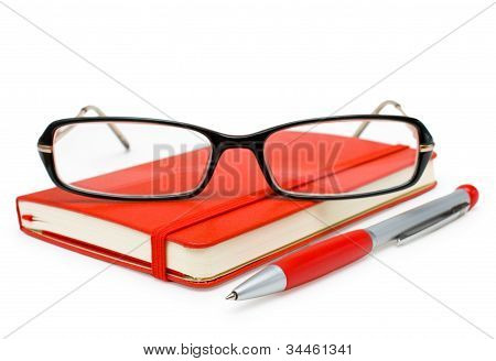 Red Closed Notepad, Glasses And Pen Isolated On White