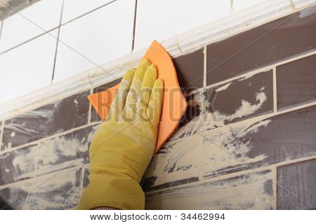 Contractor grouting ceramic tiles on a wall