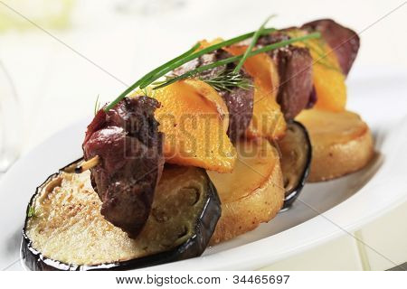 Meat and orange skewer on American potatoes with eggplant on a white tray
