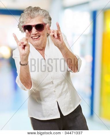 portrait of a happy senior woman doing a rock symbol indoor