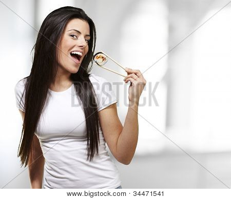 woman holding a sushi piece with chopsticks, indoor