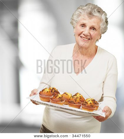 portrait of a senior woman showing homemade muffins indoor