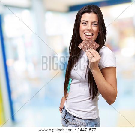 portrait of a young woman eating a chocolate bar indoor