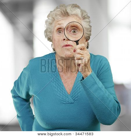 portrait of a senior woman looking through a magnifying glass, indoor