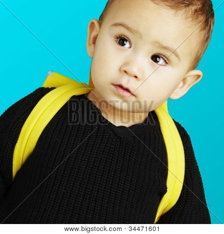 portrait of an adorable kid carrying a yellow backpack over a blue background