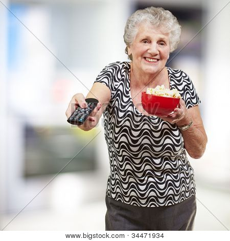 portrait of a happy senior woman looking at the tv at a living room