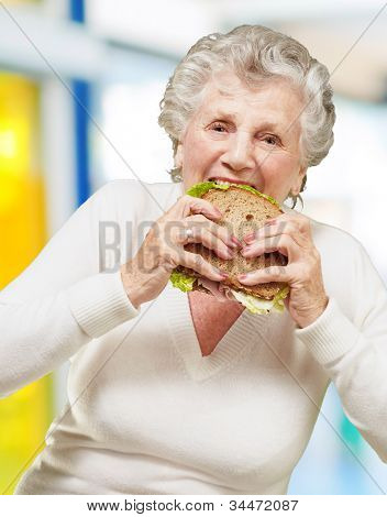 portrait of a senior woman eating a vegetable sandwich indoor