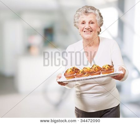 portrait of a senior woman showing a chocolate muffin tray indoor