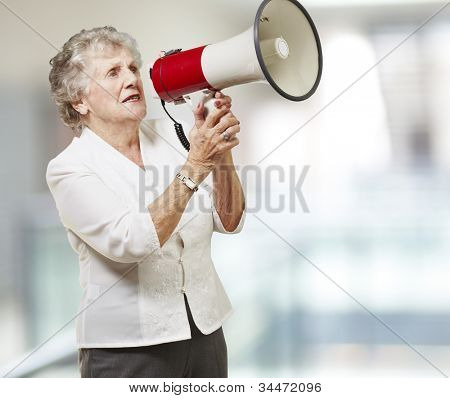 portrait of a senior woman holding a megaphone against an abstract background