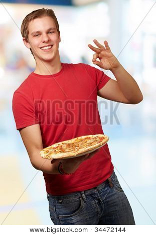 portrait of a young man holding a pizza and doing a good gesture indoor