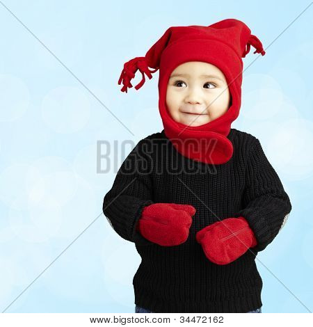 portrait of an adorable kid smiling wearing winter clothes against a blue background