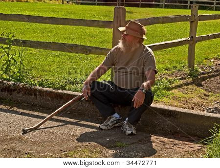 Older Man Sitting Down With Cane And Smoking