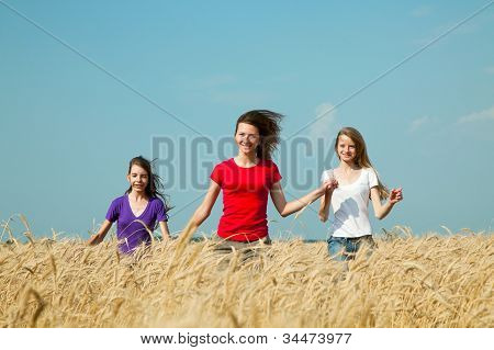 Teen Girls Running At The Wheat Field