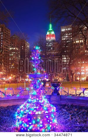 New York City Madison Square park view with Christmas decoration lights and Empire State Building.