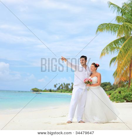 A bride holding a bouquet and groom looking towards, shot on a beach at Kuredu island, Maldives, Lhaviyani atoll