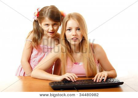 teen and child girls looking with interest in monitor, isolated on white