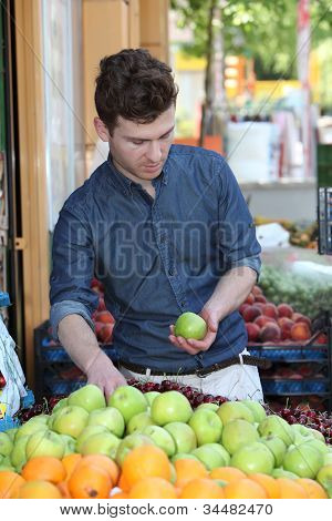 Young Customer Choosing Fruits At Grocery