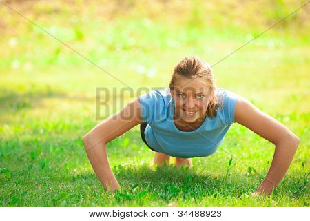 Young beautiful caucasian woman doing push up exercise on green grass at park