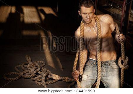 Muscular man holding rope