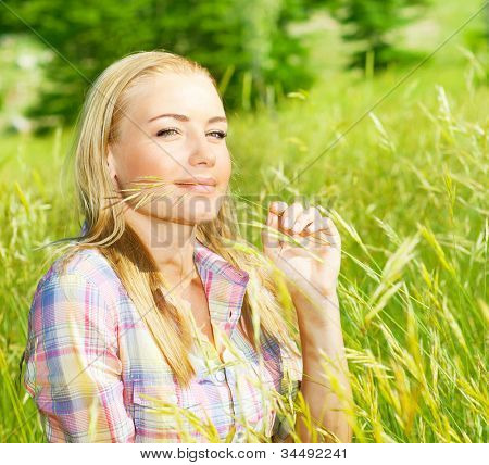 Cute blond girl on wheat field, woman sitting on green grass, female relaxing outdoor, happy pretty teen girl holding rye, young lady enjoying nature, summer rural vacation, closeup face portrait