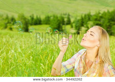 Cute girl blowing bubbles outdoors, beautiful woman spending summer holiday in park, happy female enjoying spring vacation, young lady playing on wheat field, pretty teenager relaxed outside