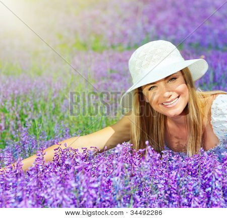 Pretty woman lying down on lavender field at sunny day, beautiful female sitting on purple flowers meadow, cheerful smiling girl enjoying violet floral glade and sun light, portrait of young lady