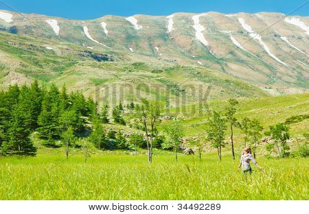Happy healthy women over mountain landscape, cute girl enjoying fresh air, beautiful female relax outside, pretty young lady looking up on blue sky, travel, vacation and summer holiday concept