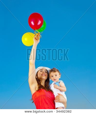 Happy family holding colorful air balloons over blue sky background, mother and adorable child baby boy playing games outdoor, mum and kid having fun in summer nature, hands up, freedom joy concept