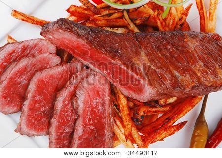 meat and potato : rare grilled beef steak served with pepper and tomato over plate isolated on white background