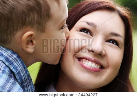 Boy kissing her mother at cheek