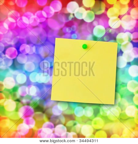 Sticky note on glowing colorful magical neon light background.