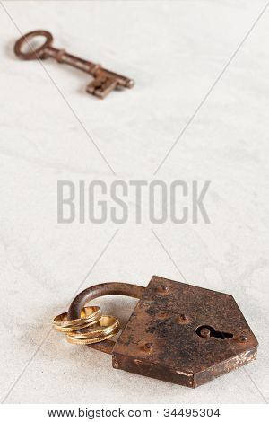 Rusty old padlock with key and wedding rings