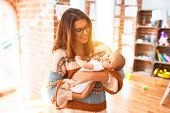 Young beautiful woman and her baby standing at home. Mother holding and hugging newborn poster