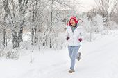Running Sport Woman. Female Runner Jogging In Cold Winter Forest Wearing Warm Sporty Running Clothin poster