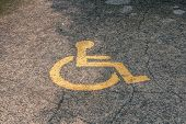 Yellow Handicapped Symbol Of Wheelchair Painted On Asphalt On A Parking Lot, Sign Of Parking Space F poster