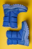 Winter Water-repellent Boots In Blue With A Gray Sole On A Yellow Background. poster