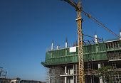 Crane And Building Construction Site Against Blue Sky. Metal Construction Of Unfinished Building On  poster
