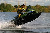 stock photo of jet-ski  - a jet ski and its rider leap clear of the water - JPG