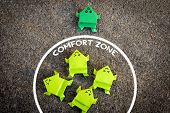 Exit From The Comfort Zone Concept. Dark Green Frog Jump Out Of The Comfort Zone While Other Light G poster