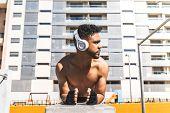 Latin American Man Training Outdoors Wearing Headphones. poster